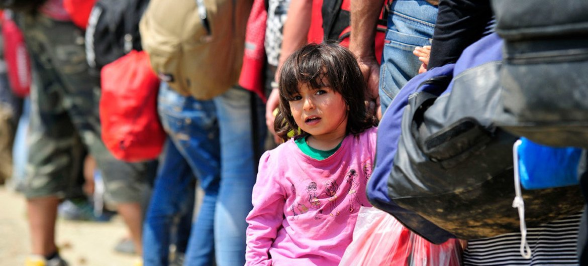 Near the town of Gevgelija, former Yugoslav Republic of Macedonia, a young Syrian girl holds the hand of an adult waiting to board a train to the Serbian border.