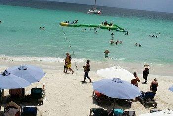 Des touristes à la plage de Negril, en Jamaïque. Photo ONU/Stan Reynolds