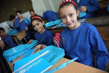 Girls in Damascus, Syria, shown in their classroom with school bags and stationery supplies they received from UNICEF and partners.
