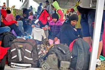 Refugiados se protegen de la lluvia bajo un toldo metálico en la frontera de Grecia y la ex República Yugoslava de Macedonia. Foto de archivo: UNICEF/Tomislav Georgiev