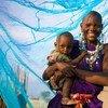 Una madre con su hijo bajo una mosquitera tratada con insecticida en Arusha, Tanzania. Foto: UNICEF/Hallahan