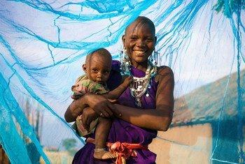 Une mère souriante avec son jeune garçon sous un filet insecticide, à Arusha, en Tanzanie. Photo : UNICEF / PFPG2014-1191 / Hallahan