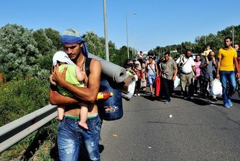Syrian man carrying a baby along the highway with other refugees, several kilometres after leaving Budapest, Hungary, heading in the direction of Vienna, Austria.
