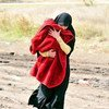 A woman carrying a child under a blanket walks on a muddy path in the southern Serbian town of Preševo, on the border with the former Yugoslav Republic of Macedonia.