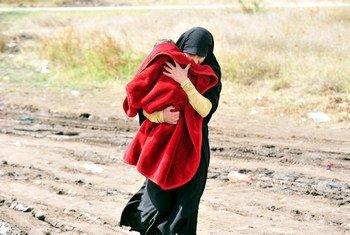 Une femme portant un enfant sur un chemin de terre dans le sud de la Serbie, à la frontière avec l'ancienne République yougoslave de Macédoine. Photo UNICEF/Tomislav Georgiev