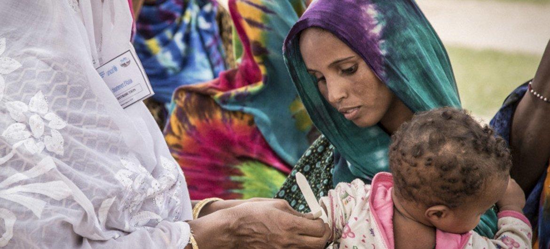 Un agent de santé mesure le bras d'une petite fille dans le centre du Niger. Si elle souffre de malnutrition, elle sera dirigée vers un centre de santé pour y être soignée. (archive)
