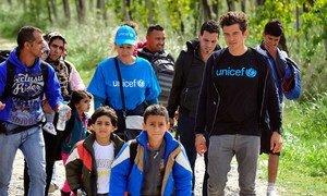 L'Ambassadeur itinérant de l'UNICEF Orlando Bloom entourés des enfants et d'adultes marche en direction du centre d'accueil de réfugiés et de migrants près de la ville de Gevgelija, en ex-République yougoslave de Macédoine. Photo : UNICEF / Tomislav Georgiev