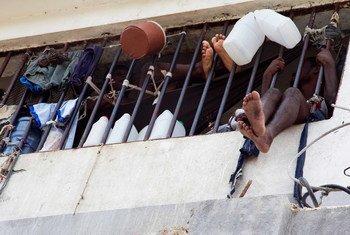 Dois detidos atrás das grades dos muros da prisão na Penitenciária Nacional do Haiti