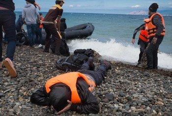 Un réfugié couché sur le ventre se couvre le visage après avoir atteint la rive, près du village de Skala Eressos, sur l'île de Lesbos, dans la nord de la Grèce. Photo : UNICEF / Ashley Gilbertson VII
