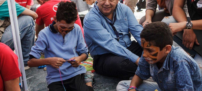 El Alto Comisonado de la ONU para los Refugiados, António Guterres, junto a dos niños sirios que juegan a la Playstation en el Centro de Identificación de Moria, en Lesbos. Foto: ACNUR/A. Zavallis