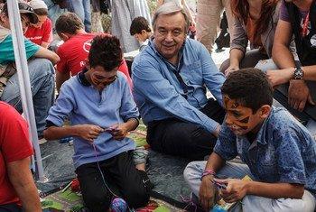 Антонью Гутерриш cидит   с мальчиками  из Сирии, которые играют электронные  игры  на острове Лесбос, Греция. Фото  УВКБ/ А.Заваллис