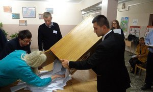 Member of a polling station committee for Belarus' presidential election empty a ballot box prior to counting in Minsk, 11 October 2015.