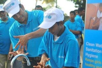 UNICEF Ambassador for South Asia, cricketing legend Sachin Tendulkar, teaches correct handwashing to a student in Colombo, Sri Lanka, 12 October 2015.