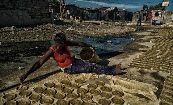 Mulher prepara bolos de barro, discos de barro, manteiga e sal que se tornaram um símbolo da pobreza extrema e fome no Haiti.