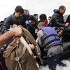 A group of refugees disembark from an inflatable boat after reaching the Greek island of Lesvos (30 September 2015).