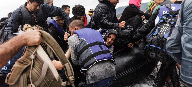 Un groupe de réfugiés débarquant d'un bateau pneumatique en arrivant sur l'île grecque de Lesbos.