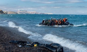 Newly-arriving refugees wave as the large inflatable boat they are in approaches the shore, near the village of Skala Eressos, on the island of Lesbos, in the North Aegean region of Greece.