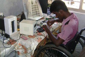 Un joven con discapacidad trabajando en una compañía de reparación de teléfonos móviles en Sri Lanka. Foto: OIT