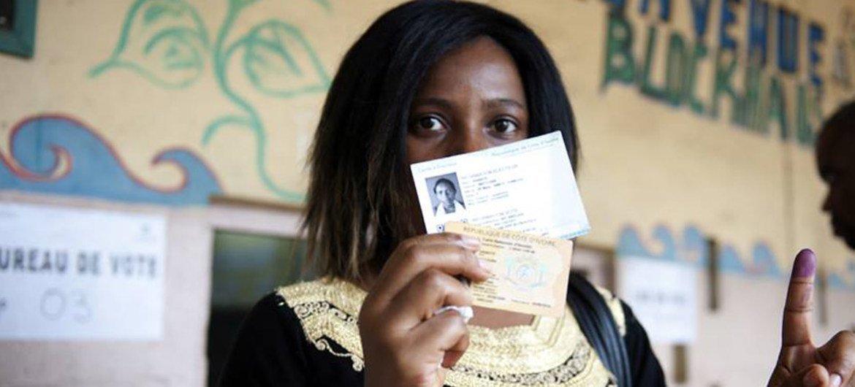 An Ivorian woman displays proof of voting in Abidjan, October 2015.