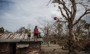 A child and an elderly man stand on the roof of a building damaged when Cyclone Pam hit Vanuatu in March 2015.