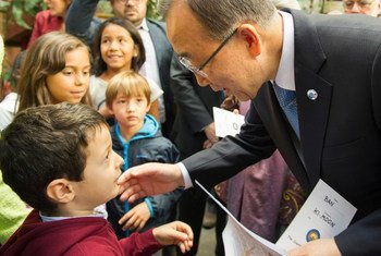 Secretary-General Ban Ki-moon (right) greets a young boy at the Centre Tenda Di Abramo in Rome, during a visit on 17 October 2015.