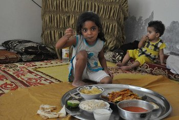 An internally displaced child in Homs, Syria, enjoys a meal.