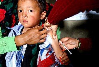 Un jeune garçon est vacciné contre la rougeole et la rubéole dans un centre de santé du district de Gorkha, au Népal.