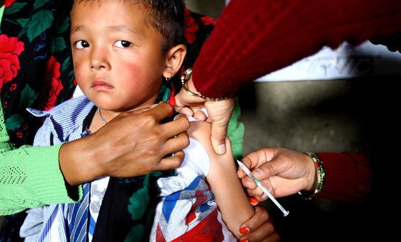 A young boy is administered measles and rubella vaccine at a health post in Gorkha District, Nepal.