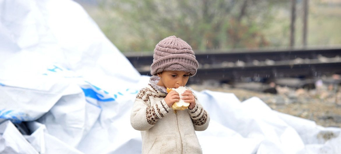 A young child eats a sandwich next to the tarpaulin that serves as a makeshift shelter, close to the town of Gevgelija, Former Yugoslav Republic of Macedonia, on the border with Greece (September 2015).