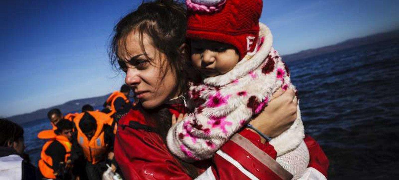 Una voluntaria en la isla griega de Lesbos asiste a una bebé recién llegada en un bote inflable. Foto: ACNUR/Achilleas Zavallis