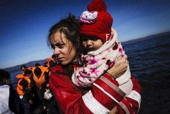 希腊莱斯沃斯岛,一名志愿者抱起一个刚刚从橡皮艇上登岸的小女孩。