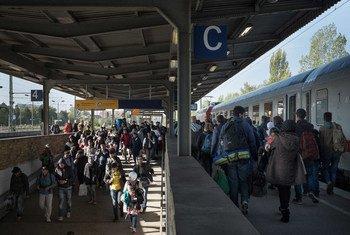 Wahamiaji na wakimbizi kutoka nchi tofauti wakiwasili kwa treni maalumu katika mji wa Berlin Ujerumani