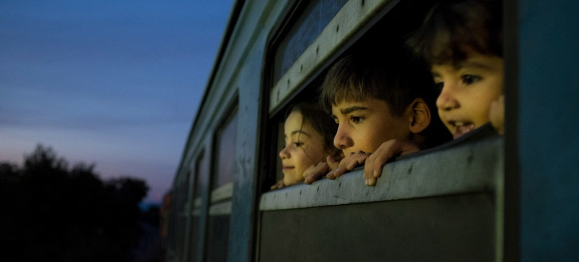 Children look out a train window at a reception centre for refugees and migrants in the former Yugoslav Republic of Macedonia.