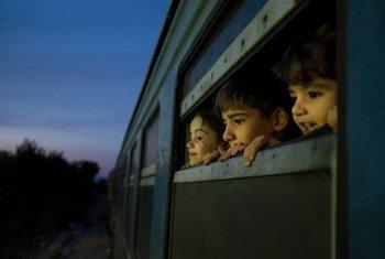 Les enfants regardent par la fenêtre de train dans un centre d'accueil pour les réfugiés et les migrants situé dans l'ex-République yougoslave de Macédoine.