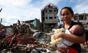 Une femme et son bébé au milieu des débris et d'autres destructions causées par le typhon Haiyan aux Philippines, en 2013.