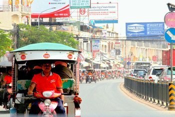 Tuk-tuk drivers dressed in orange participate in a parade on 25 October 2015 in Phnom Penh, Cambodia, to raise awareness and promote ending violence against women and girls in their community.