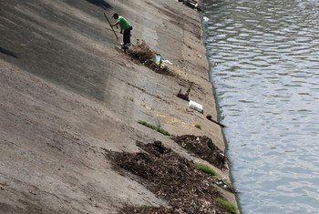 In Pasig, Philippines, a city worker cleans the Manggahan Floodway, built to reduce flooding along the Pasig River during the rainy season.
