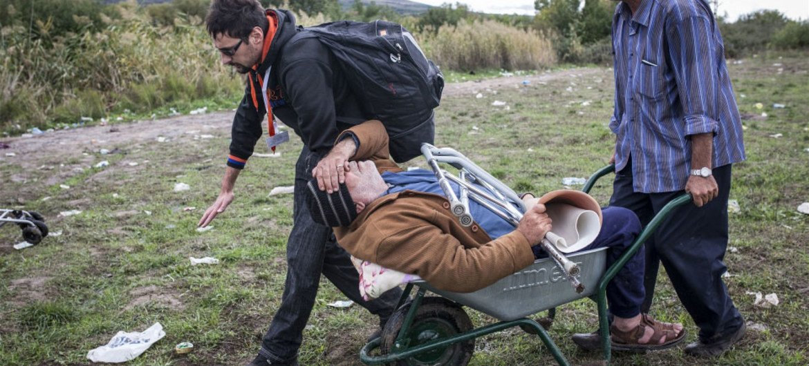 An aid worker helps pull a disabled Syrian refugee, who lost his leg to diabetes, through the no man's land between Macedonia and Serbia.
