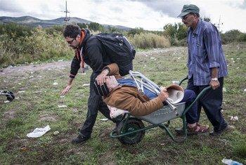 सहायता कर्मी सीरिया के एक विकलांग हुए शरणार्थी की मदद करते हुए. डायबटीज़ के कारण उसकी टाँग जाती रही. कोविड-19 से बचाव में भी विकलांगों को विशेष सहायता की ज़रूरत है.