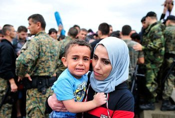 A woman holds a young boy whose face bears signs of distress, near the town of Gevgelija, former Yugoslav Republic of Macedonia, on the border with Greece.