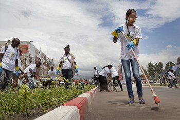 UN Volunteers and members of local organizations clear a busy road as part of activities for International Volunteer Day in Goma, eastern Democratic Republic of the Congo (DRC).