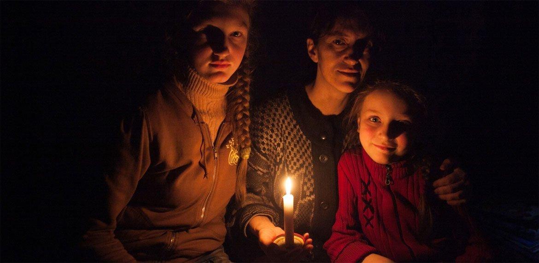 Женщина  и две ее  дочки  со свечами  в  бомбоубежище  в пригороде  Дебальцево в  Донецкой области,  Украина. Фото ЮНИСЕФ/ Алексей Филиппов