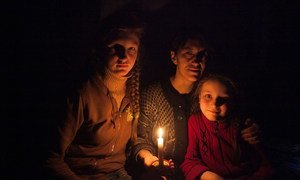 A woman and her daughters sit in candlelight in a bomb shelter on the outskirts of the city of Debaltsevo in Donetsk Oblast, Ukraine.