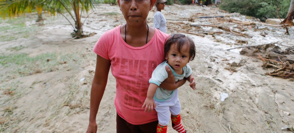 A mother carries her daughter as they evacuate from Typhoon Koppu-hit town of Laur, Philippines, on 19 October 2015. The ongoing El Niño pattern is likely to be one of the strongest since 1998 and will continue into early 2016.