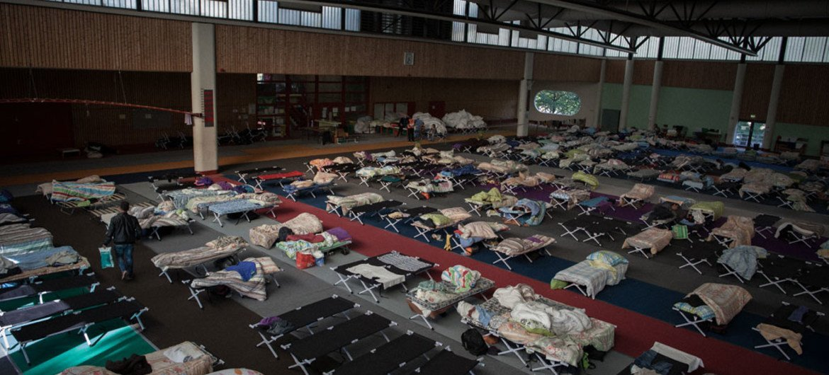 Migrants and refugees from countries including Iraq, Syria, Pakistan, and Afghanistan, as well as regions of the Balkans and Africa at an emergency shelter  at Olympia Stadium in Berlin, Germany.