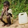A little girl waits to fill her water container in the village of Kikonka, Bas-Congo province, Democratic Republic of Congo.