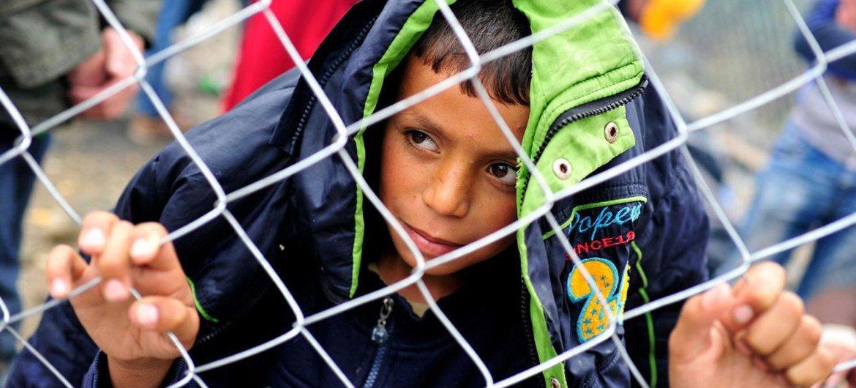 2015年9月的一个雨天,一名难民男孩在希腊与前南斯拉夫马其顿共和国边境揪着铁丝网窥看。儿基会图片/联合国新闻中心图片196199/Georgiev