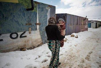 В январе 2015  года женщина  несет младенца  в  лагере  для беженцев  в долине  Бека.  Фото ЮНИСЕФ/179012/Романзи
