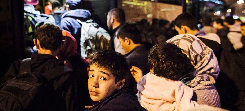En un puerto de Grecia, un niño y su familia, junto a otros refugiados e inmigrantes, intentan subir a un autobús que los llevará al centro de Atenas. Foto ACNUR/Achilleas Zavallis.