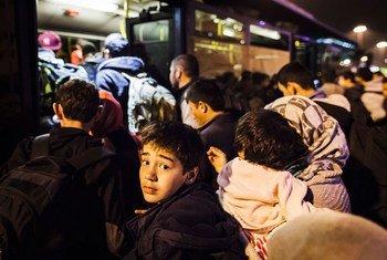 Dans un port en Grèce, un jeune garçon et sa famille rejoignent d'autres réfugiés et migrants qui tentent de monter à bord d'un autobus qui les transportera au centre d'Athènes. (archives)